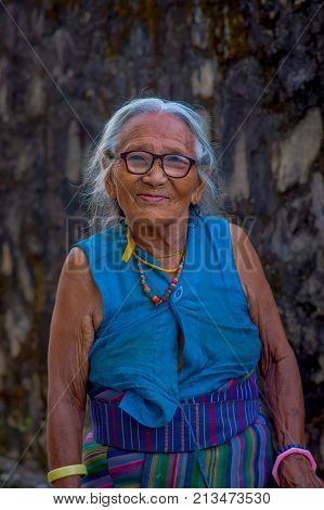 POKHARA, NEPAL - OCTOBER 06 2017: Close up of old Tibetan woman posing for camera in Tashi ling village. Tashi Ling is one of the tibetan refugee camp in Nepal.