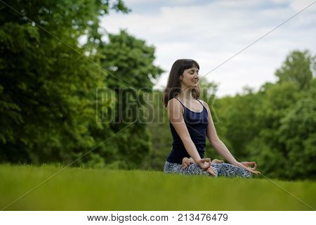 Beautiful young fit woman meditating, breathing, sitting with crossed legs in Lotus Posture in the park on summer day, copy space. Down view