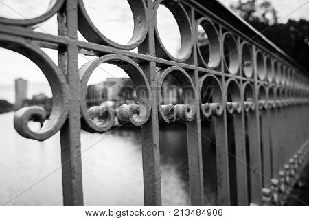 Wrought iron barricade detail in selective focus with defocused city skyline background.