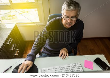 Active senior working at home running his small business