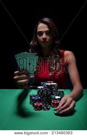 Gorgeous young woman sitting on poker table and playing poker