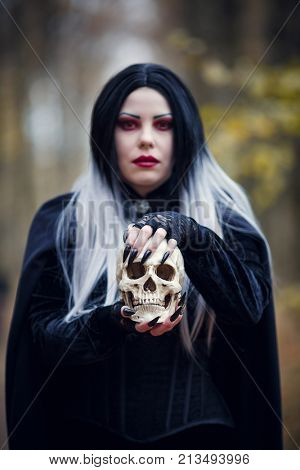 Photo of vampire girl in black cloak with skull in hands on blurred background of autumn forest