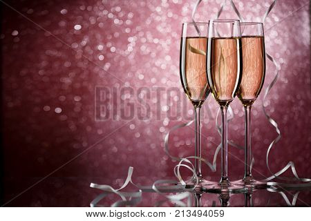 New Year picture of three glasses with wine with white ribbons on pink background, glitter effect
