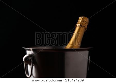 Image of bottle of champagne in iron bucket on black background