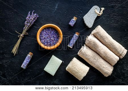 Set for foot spa with lavender. Flowers, spa salt, pumice stone, soap on black background top view.