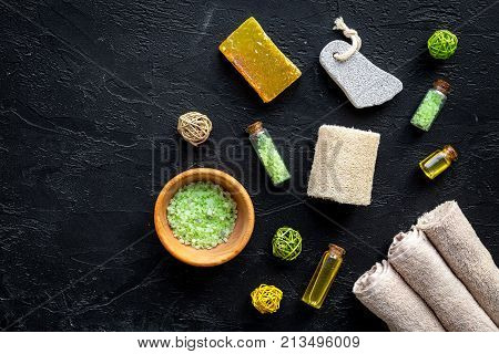 Foot spa cosmetics. Spa salt, pumice stone, soap and towel on black background top view.