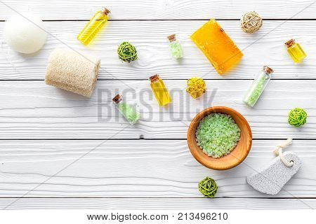 Foot spa cosmetics. Spa salt, pumice stone, soap and towel on white wooden background top view.
