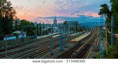 Aerial panoramic view of the Sochi railway station with many railroads and traction line towers at sunset Russia