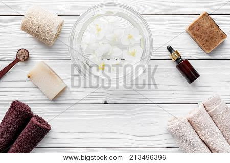 Bath in bowl with tropical flowers for foot spa, pumice stone, soap and oil on white wooden background top view.