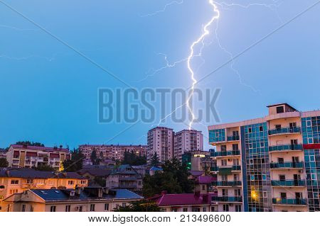 View of apartment buildings on the mountain with lightning during a morning thunderstorm Sochi Russia