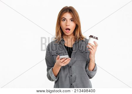 Portrait of a shocked pretty girl holding mobile phone while drinking coffee and looking at camera isolated over white background