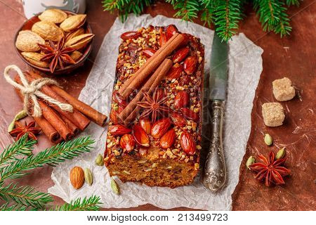 Homemade holiday Fruitcake with nuts fruits and spices. Almonds cinnamon star anise cardamom on the table. Traditional English pastries. Christmas. New year. Selective focus