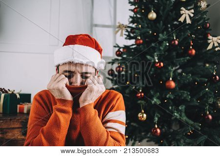 Cozy and nice picture of a guy wearing traditional Christmas clothes. Young man is sitting on the floor hear beautiful and green pine tree and relaxing. He is full of calm, joy and happiness. Cut view
