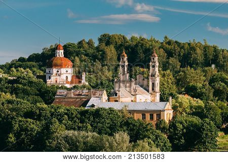 Vilnius, Lithuania. View Of Church Of The Ascension And Church Of The Sacred Heart Of Jesus Among Green Foliage.