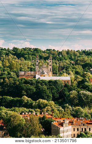 Vilnius, Lithuania. View Of Old Catholic Church Of Ascension Among Green Foliage In Summer Day.