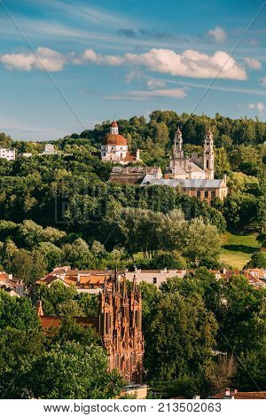 Vilnius, Lithuania. View Of Roman Catholic Church Of St. Anne, Church Of Ascension And Church Of Sacred Heart Of Jesus Among Green Foliage In Old Town In Summer Day. Unesco World Heritage