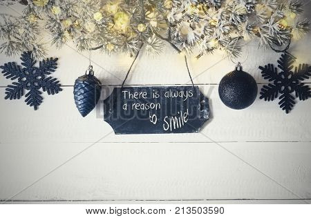 Black Chirstmas Plate With English Quote There Is Always A Reason To Smile. Fir Branch With Fairy Lights On Wooden Background. Black Christmas Decoration Like Balls And Snowflakes.