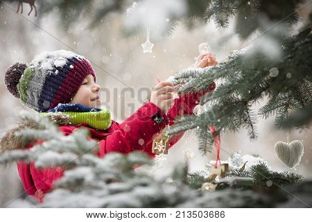 Happy smiling kid boy decorating Christmas tree in winter snow park. Child having fun. Christmas celebration outdoors. Winter and holidays concept.