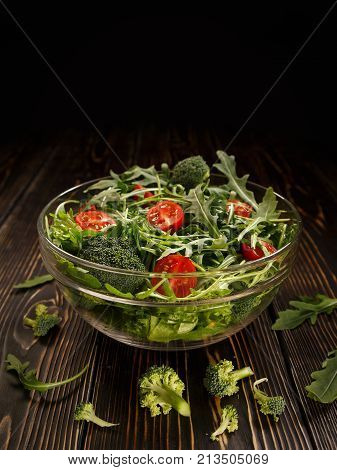 Glass dish with organic salad from broccoli arugula and cherry tomatoes is on the table