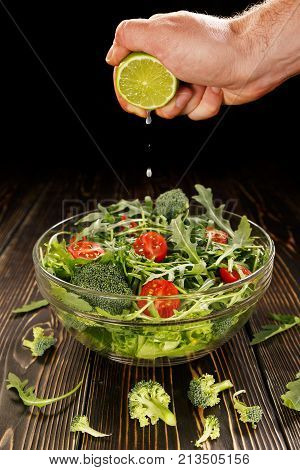 Lime juice is squeezed into a glass dish with salad