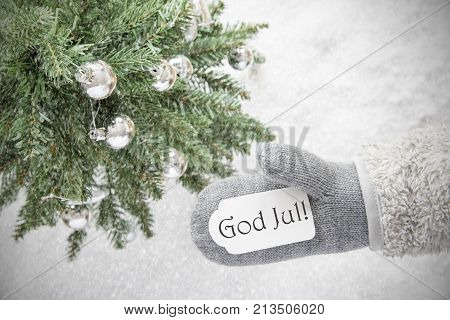 Glove With Label With Swedish Text God Jul Means Merry Christmas. Green Christmas Tree With Silver Balls On Snow In Background. Seasonal Greeting Card With Snowflakes.