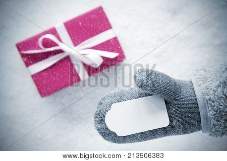 Glove With Label Copy Space For Advertisement. Rose Gift Or Present On Snow In Background. Seasonal Greeting Card With Snowflakes.