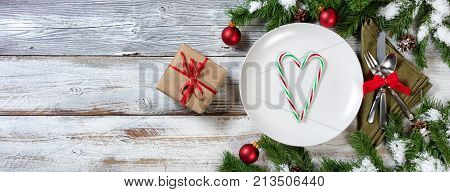 Holiday Christmas Dinner setting with gifts on rustic table with snow covered branches