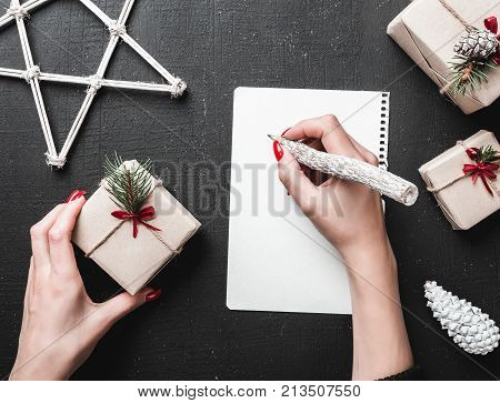 Christmas greeting card, a lady writes the gift list she will give. Xmas ambience is supplemented by the plenty of surrounding gifts