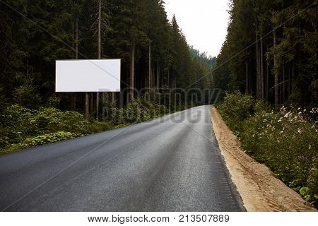 Blank billboard sign by empty highway through forest mountains landscape. Ad panel on road. Forest road with white billboard for your text. mock up