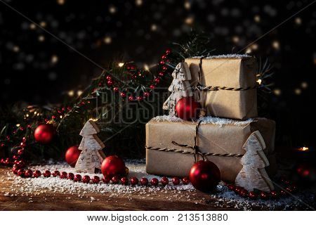 christmas gift boxes in kraft paper decorated with red baubles fir branches and small wooden trees some snow and bokeh lights dark rustic background with copy space selected focus narrow depth of field