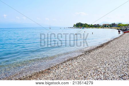 Kamena Vourla Greece - July 14 2017: Vacationers on the pebble beach at summer sunny morning.