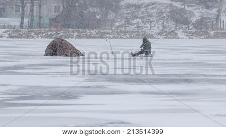 Winter sport - ice fishing. A lone fisherman, the tent on the ice in a snowstorm. An extreme sport.