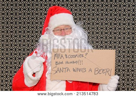 Santa Claus. Santa Claus holds a cardboard sigh with a message in felt pen. Funny Santa Claus Photo.