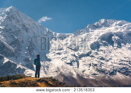 Standing young woman on the hill and looking on amazing Himalayan mountains. Landscape with traveler high rocks with snowy peaks blue sky in autumn in Nepal. Lifestyle travel. Trekking in Himalayas