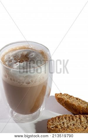 Frothy cappuccino coffee with grated nutmeg and almond biscotti. Close up of hot drink in double walled glass with amaretti biscuits. White background with copy space.