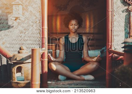 Young charming African American female with curly hair sitting inside of oriental pagoda on a matting and meditating halo appeared around her head she is feeling peaceful and calm reached nirvana