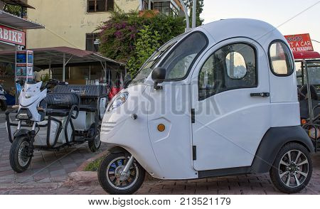 KEMER TURKEY - OCT 2 2017: Mini car for one person and a motorcycle for rent near motorcycles storage.
