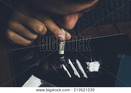 Man taking or sniffing drugs from tablet, snorting cocaine, Drug abuse and bad habbit concept, dark toned