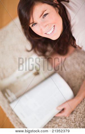 Süße Frau, eine Zeitschrift lesen, beim liegen auf dem Teppich im Wohnzimmer