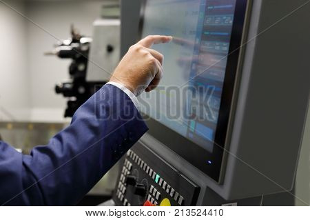 A service engineer using the touch screen to prepare cnc metalworking center for a new task. Selective focus.