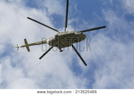 Helicopter flies against a blue sky background. Transport