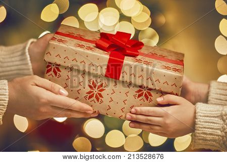 Merry Christmas and Happy Holidays! Hands of parent giving a x-mas gift to child.