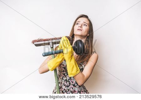 Prying girl hates cleaning,in yellow rubber gloves, holds a plunger