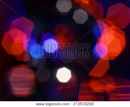 Silhouette of a womanâ??s head surrounded by red, white and blue bokeh.