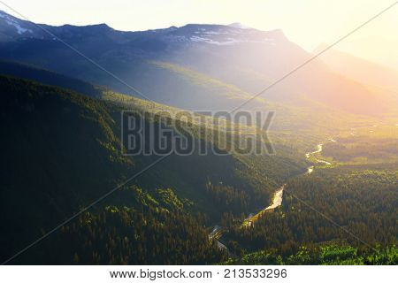 Sun begins to set over the mountains at Logan Creek in Glacier National Park, Montana