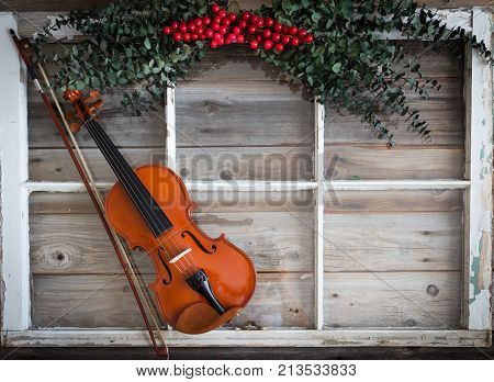 image of a violin lying on a rustic wood surface with a white window frame and green holly with red berries.