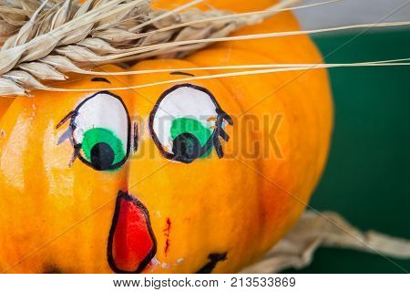 extreme close up of orange pumpkin with face drawn on it