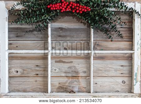 background image of a white window frame lying on a rustic wood background with a green fern with red berries hanging on top of the frame great for copy space.
