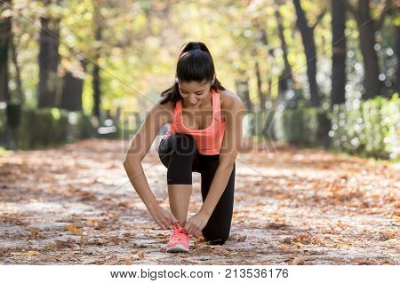 young beautiful and attractive sport runner woman tying her shoe sneaker laces smiling happy ready for running and jogging workout at city forest park in a beautiful Autumn morning