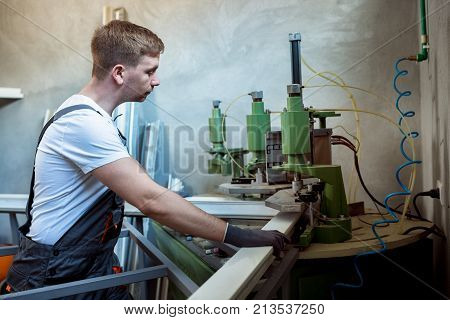 Worker Operating Welding Machine In Factory.